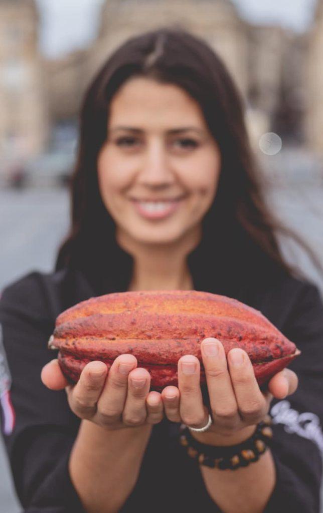 Hasnaâ présente une cabosse de cacao