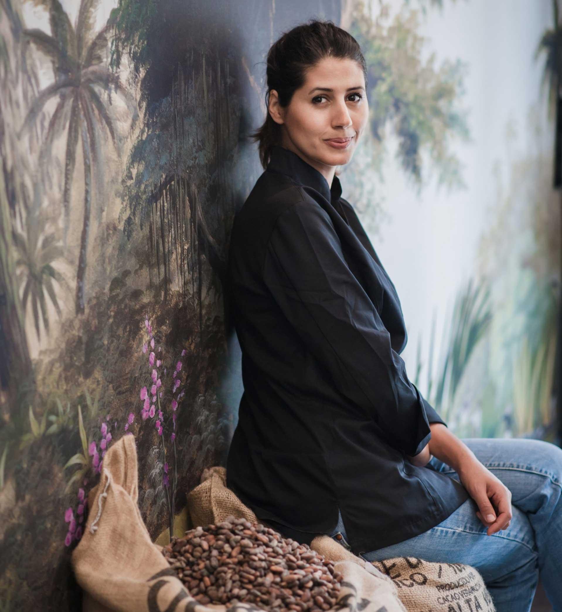 Portrait de Hasnaâ Ferreira assise sur un banc à coté de fèves de cacao